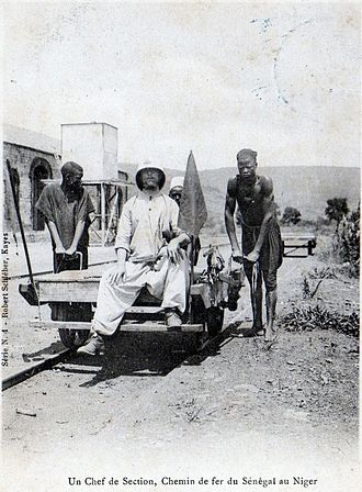 "French West Africa - A ""Section Chief"" in the building of the Dakar–Niger Railway, pushed by African workers, Kayes, Mali, 1904"
