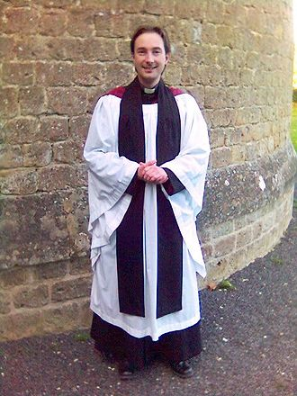 Surplice - An Anglican priest wearing a cassock, academic hood, English-style surplice, and tippet as his choir dress.