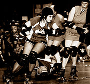 Black and white picture of several women on roller skates coming around a curve in a roller derby track