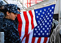 Defense.gov News Photo 110104-N-4590G-082 - U.S. Navy Quartermaster Seaman Ingrid Devinkayne prepares a national ensign to be raised as the aircraft carrier USS Ronald Reagan CVN 76 leaves.jpg