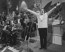 Zwart-witfoto van de wedstrijd van 1958 in de AVRO Studio's in Hilversum, Nederland;  een orkest zit links van een klein podium, met de Italiaanse zangeres Domenico Modugno die op het podium voor een muur zingt.