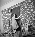 Doreen Buckner draws the curtains in her family's London home to comply with the nightly 'Blackout' during the Second World War. D17275.jpg