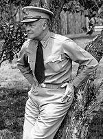 a man in a military uniform is leaning casually against a tree hands on hips holding a cigarette