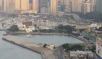 Kellett Island - Kellett Island in 2004, viewed from the west. The Royal Hong Kong Yacht Club buildings are visible on the left, the entrance of the Cross-Harbour Tunnel is visible on the right, and the Causeway Bay Typhoon Shelter in the background.