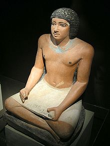 A painted, realistic stone statue of a black-haired, perhaps middle-aged man sitting cross-legged while holding a stone-carved depiction of a papyrus reading scroll in his lap
