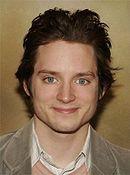 Jeune homme brun aux yeux bleus et souriant.