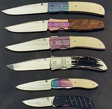 An assortment of knives with anodized titanium bolsters in bright colors