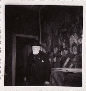 "James Ensor - Ensor in front of ""Entry of Christ into Brussels"" in his house in Ostend, 1940s, photo by Albert Lilar"