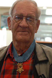 Photograph of an older white man wearing glasses and a medal hanging from a blue ribbon around his neck