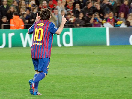 Messi pointing to the sky following his record five-goal display against Bayer Leverkusen in the last 16 of the UEFA Champions League in March 2012 FC Barcelona - Bayer 04 Leverkusen, 7 mar 2012 (07).jpg