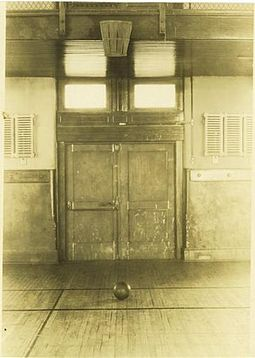 "The original 1891 ""Basket Ball"" court in Springfield College. It used a peach basket attached to the wall. Firstbasketball.jpg"