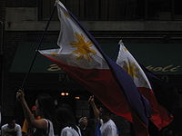 Individuals marching in New York City with Philippine flags.