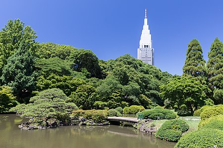 Footbridge over a pond in Shinjuku Gyoen National Garden and NTT DoCoMo Yoyogi Building, Tokyo