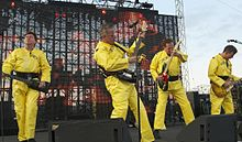 Devo on stage, wearing their trademark bright yellow costumes