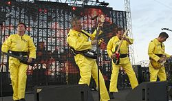 Devo onstage in their trademark bright yellow costumes