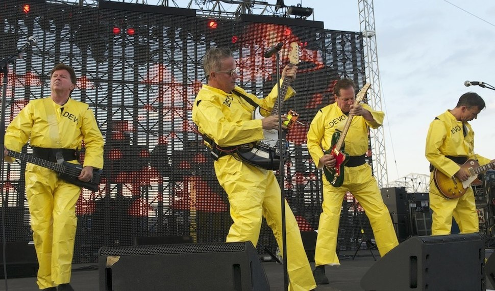 Devo onstage, wearing their trademark bright yellow costumes
