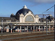 Train station with large, domed building and a high-speed train at the platform
