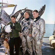Three men, two of them in space suits, stand on a vessel