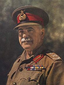 Head and shoulders colourised photograph of General Sir Thomas Blamey, KCB, CMG, DSO taken circa 1942. Blamey has a grey moustache and is wearing a peaked cap with scarlet cap band and general's bullion cap badge and an Australian Army khaki shirt to which are attached Australian general's embroidered rank slides, general's gorget patches in scarlet with gold bullion oakleaves and three ribbon bar rows for his various orders, decorations and medals.