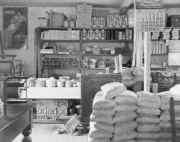 "Packaged and loose goods are stacked on shelves and the floor. Items visible on the walls include a calendar showing ""July 1936"" and a Coca-Cola advertisement. Visible items for sale include loose dishes, lanterns, dustpans, padlocks, rope, Mason jars, boxed soaps, boxes of shot-gun shells, canned goods, bags of self-rising flour. Rolls of butcher-paper visible at left. A safe is at centre, partially behind bags of flour."