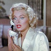 Monroe in Gentlemen Prefer Blondes. She is wearing a white dressing gown and is holding a phone, she looks shocked, with wide eyes and an open mouth.