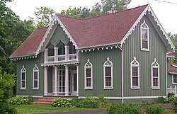 A green house with a reddish roof pointed on the front and the side. It has vertical raised wood on the sides and decorative flourishes above the windows and at the roofline.