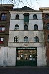 foto van Pakhuis met gepleisterde gevel onder rechte lijst met getoogde vensters. Gevelsteen: