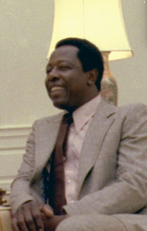 Hank Aaron wearing a suit and smiling