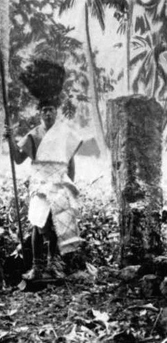 Culture of the Cook Islands - High priest (ta'unga nunui) at Arai-te-Tonga marae with the pillar stone of investiture.