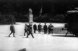 Photo noir et blanc qui est, en fait, une capture d'écran du film de propagande de l'armée américaine de 1943, Divide and Conquer (Why We Fight #3), réalisé par Frank Capra et basé en partie sur des archives des actualités de l'époque. L'image est divisée en deux. L'arrière-plan, sombre, est une lisière de forêt devant laquelle, à peu près au centre, on distingue une statue du maréchal Foch debout en uniforme sur un haut piédestal. Le reste de la photo est une étendue claire de gravier. On y distingue, au centre, de dos, Adolf Hitler entouré de quelques hauts dignitaires nazis; tous ont le regard fixé sur la statue du maréchal Foch.