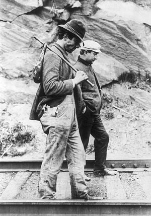 Hobo - Two hobos walking along railroad tracks after being put off a train. One is carrying a bindle.