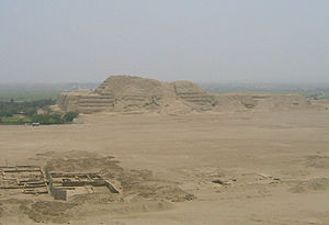 Huaca del Sol - Huaca del Sol as seen from the southeast, with the Moche River delta beyond and city ruins in the foreground.