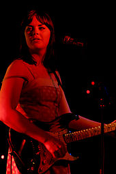 Colour photograph of Isa Maria performing live in 2007. She is playing underneath a red light, making her appear red.