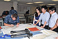 Interns from the South Korean Parliament watch as U.S. Navy Operations Specialist Seaman Recruit James Welch, left, plots a course on a navigational map at Operations Specialist-Quartermaster A School at the 120730-N-IK959-182.jpg