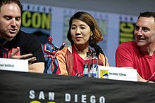 Left to right, a caucasian male with short brown hair, an asian woman with medium length brown hair and a caucasian male with short black hair sit behind a table. A small statue of a punk version of Spider-Man sits on the table in front of them.