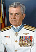 A color image of showing the head and upper torso of Stockdale wearing his military dress uniform with medals. His Medal of Honor can be seen around his neck.