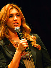 A photograph of a blonde woman speaking into a black microphone which she is holding in her right hand while wearing a black jacket