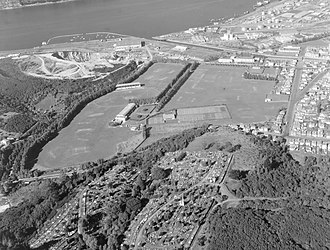 Logan Park, Dunedin - An aerial view in 1955, looking south. The Caledonian Ground had not been built, but the University Oval and former Art Gallery are clearly visible, centre left. Logan Point Quarry and the Otago Harbour are visible in the background.