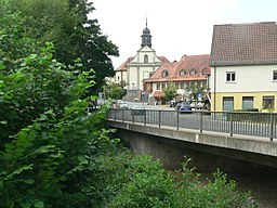 """Mömbris: In the foreground the bridge across the river Kahl, in the middle the central square called """"Am Markt"""" and behind the parish church."""