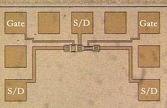 MOSFET - Photomicrograph of two metal-gate MOSFETs in a test pattern. Probe pads for two gates and three source/drain nodes are labeled.