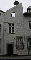foto van Huis met aan de straat een halve topgevel, gedeeltelijk met mergelbanden.