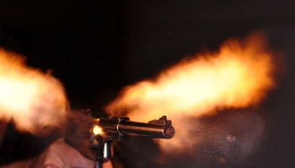 Handgun - .44 Magnum revolver and bullet, photographed with an air-gap flash.