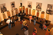 Museum goers look an exhibit of clothing from New Zealand's Toi Maori people. On the wall behind are photos of individuals wearing examples of the clothing.