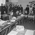 Minister-president Cals terwijl hij achter een tafeltje zit, naast een leerling…, Bestanddeelnr 918-3738.jpg