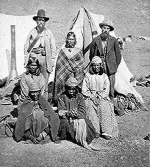 Modoc people - L to R, standing: US Indian agent, Winema (Tobey) Riddle, a Modoc; and her husband Frank Riddle, with four Modoc women sitting in the front two rows. Photographed by Eadweard Muybridge, 1873.