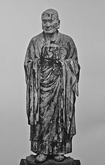 Muchaku (Asanga). Frontal view of a lifelike statue keeping his hands in front of his body with one palm turned up and the other facing sidewards as if keeping something. Black and white photograph.