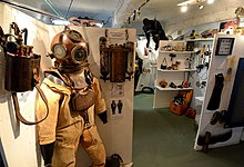 Interior view of a museum display showing standard diving dress with copper helmet in the foreground.