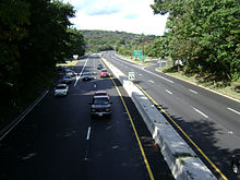 An overhead view of a four-lane divided freeway running through a wooded area. An interchange is seen in the distance.