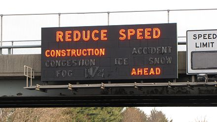 An older variable-message sign displaying a warning. These signs have since been replaced. New Jersey Turnpike Reduce Speed sign.jpg