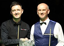 Wilson and Peter Ebdon shaking hands behind a trophy